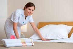 Meisje dat bed in hotelruimte maakt Stock Foto's