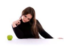 Meisje dat bij de appel staart Stock Foto's