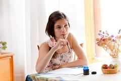 Meisje dat bij lijst door pen schrijft Royalty-vrije Stock Afbeelding