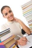 Meisje dat bij lijst met boeken schrijft Stock Foto