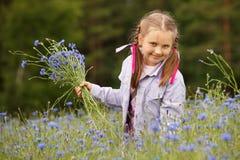 Meisje dat blauwe bloemen plukt Royalty-vrije Stock Foto's