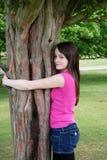Meisje dat boom koestert Stock Foto