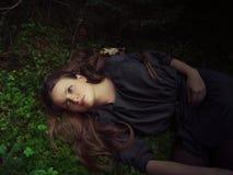 Meisje dat in bos ligt Stock Foto's