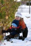 Meisje dat broer in sneeuw helpt Stock Foto