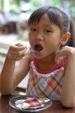 Meisje dat cake eet Stock Foto's