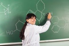 Meisje dat chemische structuur trekt op een bord stock foto