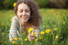 Meisje dat in de bloem van de grasgreep ligt royalty-vrije stock foto's
