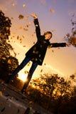 Meisje dat de herfstbladeren werpt Royalty-vrije Stock Fotografie