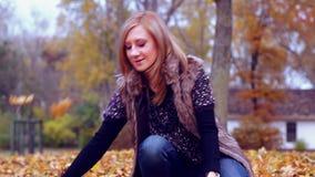 Meisje dat de herfstbladeren werpt stock footage