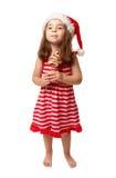 Meisje dat de holdingssuikergoed draagt van de santahoed stock afbeelding