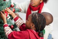 Meisje dat de Kerstboom verfraait Stock Afbeelding