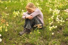 Meisje dat de lentebloem bekijkt stock foto's