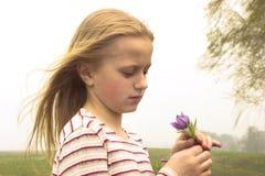 Meisje dat de lentebloem neemt stock foto