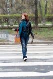 Meisje dat de straat kruist stock fotografie