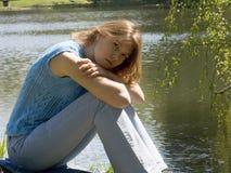 Meisje dat dichtbij vijver situeert Stock Fotografie