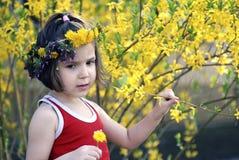 Meisje dat door bloemen wordt omringd Stock Foto's