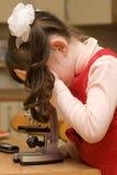 Meisje dat door de microscoop kijkt Stock Foto