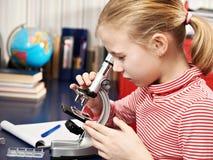 Meisje dat door een microscoop kijkt Stock Foto