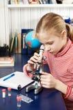 Meisje dat door een microscoop kijkt Stock Foto's