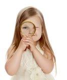 Meisje dat door een vergrootglas kijkt stock foto's