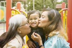 Meisje dat door haar moeder en grootmoeder wordt gekust stock fotografie