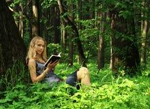 Meisje, dat een boek in een bos leest Stock Foto's