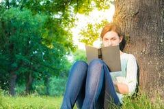 Meisje dat een boek in het park leest Stock Foto's