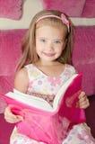Meisje dat een boek leest en op de bank situeert stock fotografie