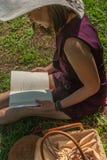 Meisje dat een boek in park leest stock afbeeldingen