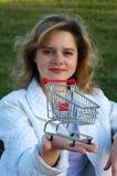 Meisje dat een boodschappenwagentje overhandigt stock foto