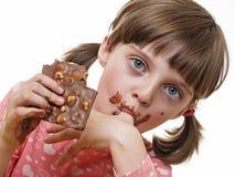 Meisje dat een chocolade eet Stock Afbeeldingen