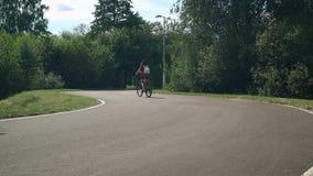 Meisje dat een fiets berijdt Zachte nadruk Bos en wolken op de achtergrond stock video