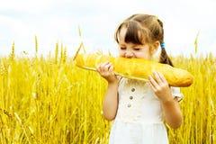 Meisje dat een lang brood eet stock afbeelding