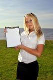 Meisje dat een leeg document houdt tegen het overzees Stock Foto