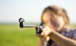 Meisje dat een pneumatisch geweer streeft stock foto's