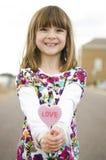 Meisje dat een rood hart houdt stock foto