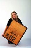 Meisje dat een zware doos opheft Stock Afbeelding