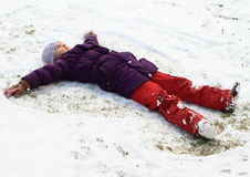 Meisje dat engel in sneeuw maakt Royalty-vrije Stock Afbeeldingen