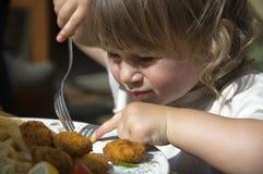 Meisje dat frieten eet stock foto's