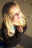 Meisje dat in gebed op strand knielt stock fotografie