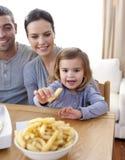 Meisje dat gebraden gerechten thuis eet Stock Foto's