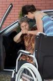 Meisje dat gehandicapte vrouw helpt die uit auto komt Royalty-vrije Stock Foto