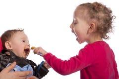 Meisje dat haar babybroer voedt Stock Afbeeldingen