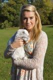Meisje dat haar konijn knuffelt Stock Afbeelding