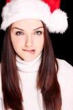 Meisje dat haar lip bijt die de hoed van de Kerstman draagt Royalty-vrije Stock Foto's