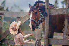 Meisje dat haar paard voedt Stock Afbeelding