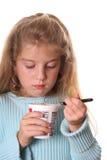Meisje dat haar yoghurtverticaal bekijkt royalty-vrije stock afbeelding