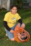 Meisje dat haar zak van Halloween vult met bladeren stock afbeelding