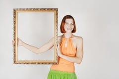 Meisje dat in heldere kleren decoratief frame houdt Stock Foto's