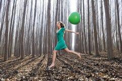 Meisje dat in het hout met een grote ballon springt Stock Afbeeldingen